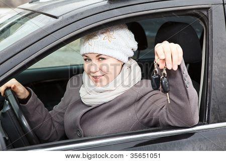 Mujer joven sentada en el coche y con encendido llaves en mano
