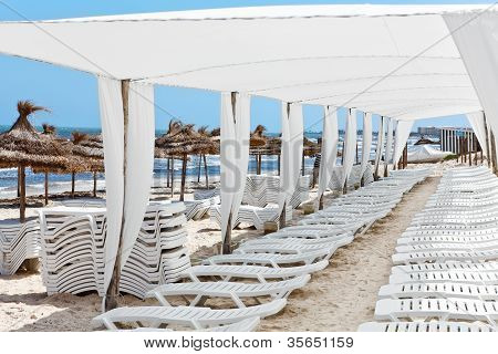 White Plastic Sunbeds In Sandy Beach Under Big Parasol