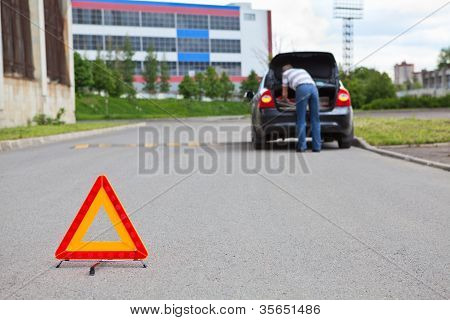 Triangle Warning Sign On Road Foreground And Driver In Car Luggage Rack