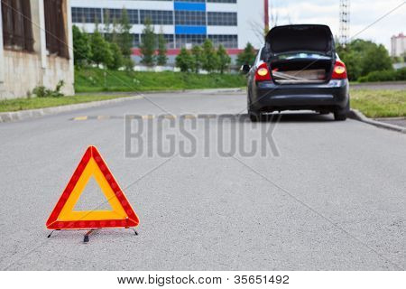 Triangle Warning Sign On Road Foreground And Broken Car With Blinker Lights On Road Wayside
