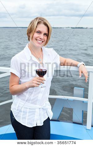 Smiling Young Woman Standing On Ship Prow And Holding Red Wine Glass In Hand