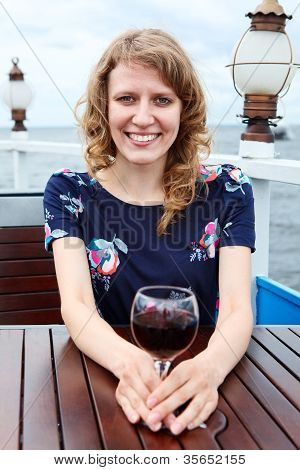 Happy Beauty Woman In Dress With Wine Glass Sitting At The Table