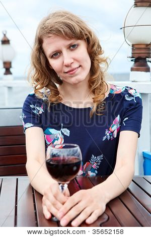 Serene Beauty Woman In Dress With Wine Glass Sitting At The Table