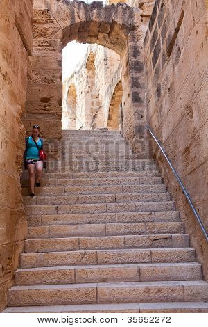 Young woman going down the stairs of Tunisian amphitheater