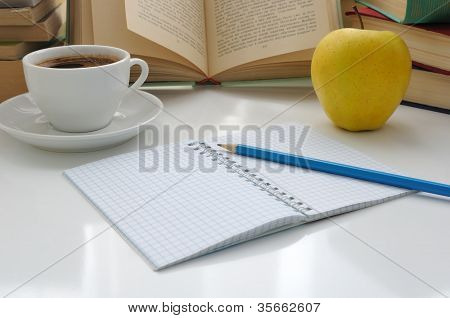 Notebook With A Pencil On A Table With A Cup Of Coffee And An Apple With Books