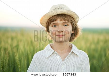 Happy Boy In The Hat Among The Wheat Field