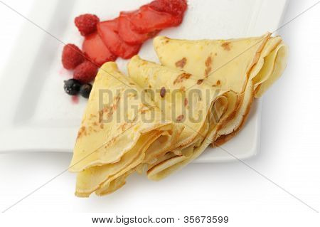 Crepe On A Plate With A Strawberry, A Raspberry And A Bilberry