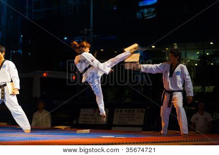 Korean Taekwondo Girl Jump Kicking Breaking Board