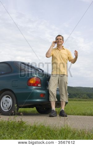 Man With Mobile Phone Beside His Car
