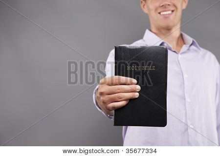 Smiling Young Man Holds Bible