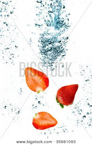Strawberry are falling in water with a big splash