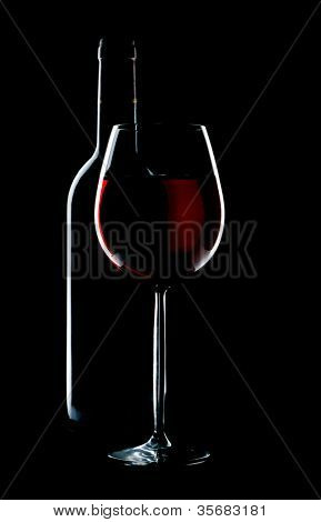 silhouette a glass and bottle on a black isolated background