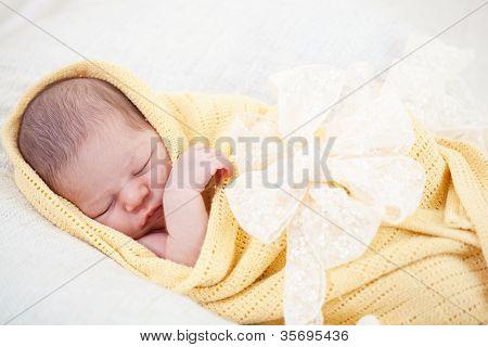 sono do bebê recém-nascido, envolvido em um cobertor amarelo