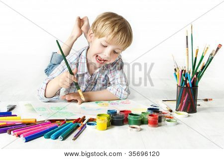 Happy Cheerful Child Drawing With Brush In Album Usin multicolor Painting Tools