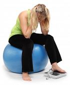 foto of anorexic  - Depressed overweight woman on a weighing machine - JPG