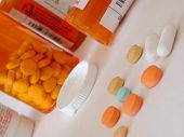 stock photo of ibuprofen  - scattered pills with the concept of over medication or addiction - JPG