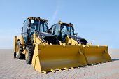 image of heavy equipment  - Two new bulldozers on a show window - JPG