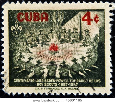 stamp printed in Cuba shows image of scouts around a campfire celebrating the centenary of scouting