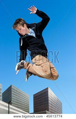 Energético garoto pulando na cidade.