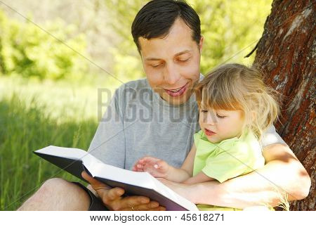Father With His Little Daughter Reads The Bible