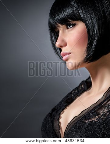 Closeup portrait of sexy woman with stylish short haircut isolated on dark background, profile of seductive brunette female with perfect makeup, beauty salon