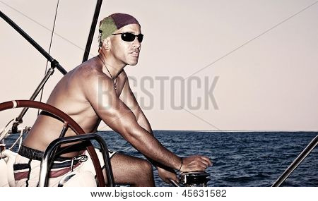Handsome strong man working on sail boat, sailor enjoys crew duty, luxury lifestyle, yachting sport, traveling the oceans, summer vacation concept