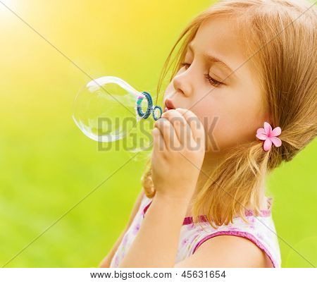 Sweet little girl blowing soap-bubbles in the garden, summer time, game outdoors, having fun, holiday concept