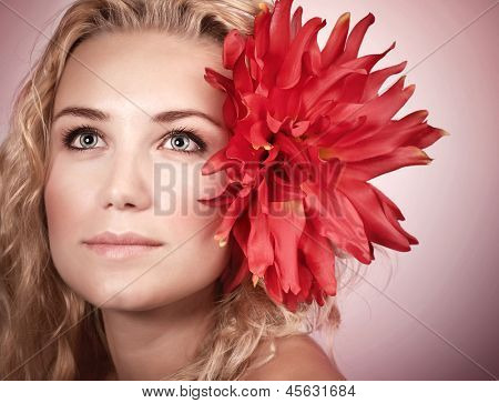 Closeup portrait of cute blond girl with big red flower in head isolated on pink background, natural makeup, spa concept