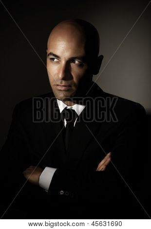 Portrait of sexy male wearing black suit, white shirt and stylish tie isolated on gray background, luxury lifestyle, business and job concept
