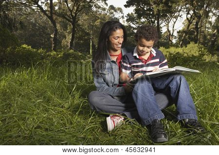 Mother and son sitting on grass and reading