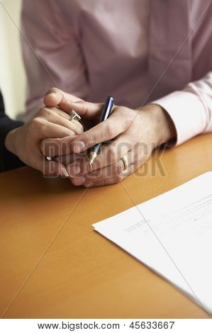 Close up of couple holding hands with pen