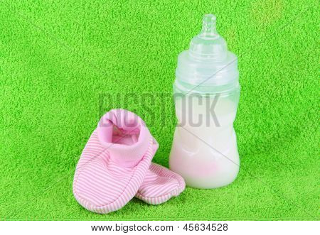 Bottle for milk and booties on towel background