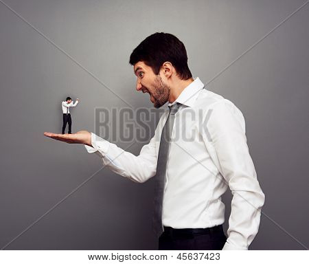 concept photo of big boss screaming at the small man over dark background