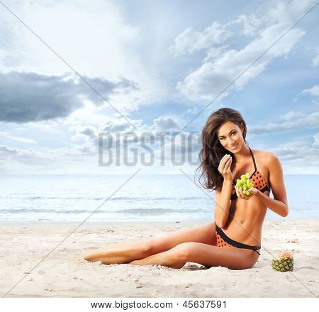 Beautiful, sporty and young woman in sexy swimsuit eating grapes on the beach