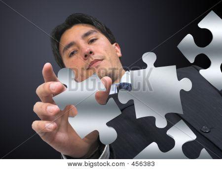 Business Man Arranging Puzzle