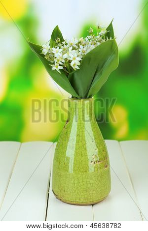 Beautiful mountain daffodils in  color vase, on wooden table on bright background