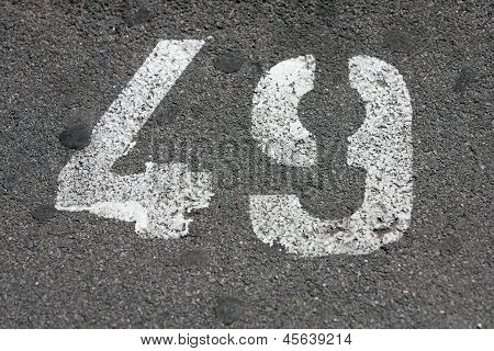 Close Up Detail Of A Number Forty Nine Painted In White On Asphalt