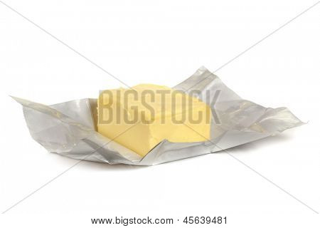Pat of butter on foil wrapper, isolated on white.