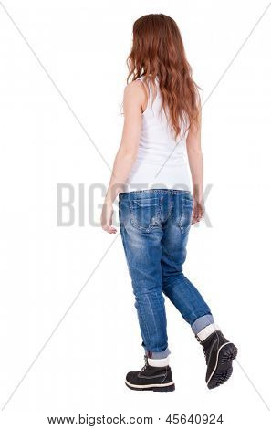 back view walking  woman . beautiful redhead girl in motion.  backside view of person.  Rear view people collection. Isolated over white background. teenager in black winter boots and jeans goes ahead