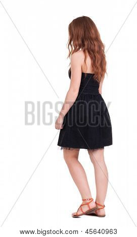back view walking young beautiful  redhead woman. girl  watching. Rear view people collection.  backside view person.  Isolated over white background. red-haired girl in a black dress stepping aside