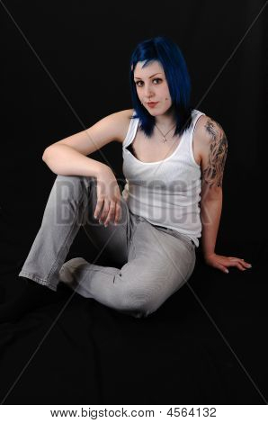 Pretty young blue haired girl in white t-shirt and jeans with a big tattoo