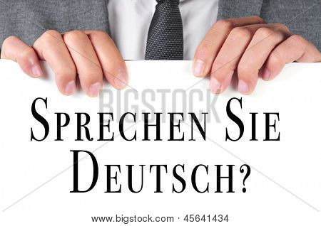 a man wearing a suit holding a signboard with the sentence sprechen sie deutsch? do you speak german? written in german on it