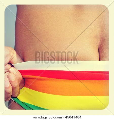 someone wearing a rainbow swimsuit on the beach, with a retro effect