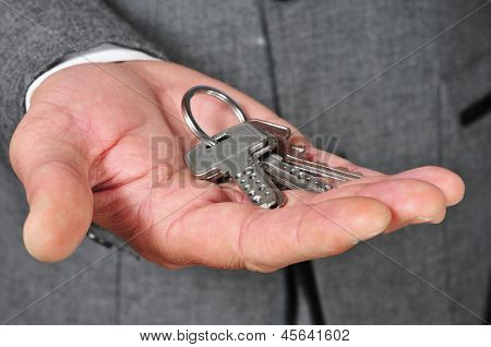 a man wearing a suit with a key ring in his hand
