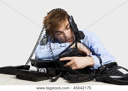 Exhausted man sitting with a bunch of phones over him