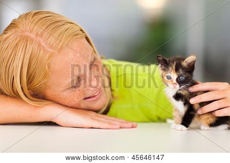 loving pre teen girl playing with her pet kitten
