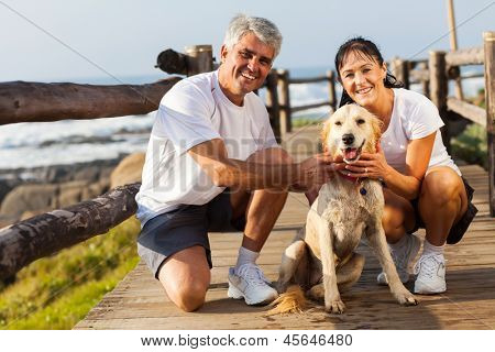 sporty middle aged couple and pet dog at the beach in the morning