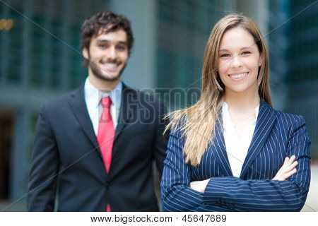 Two business people smiling outdoor in a modern city