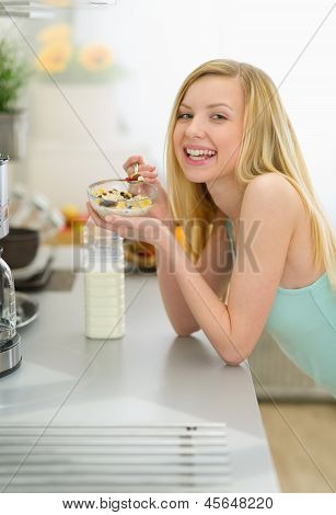 Smiling Teenager Girl Eating Breakfast In Kitchen