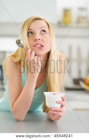 Portrait Of Thoughtful Teenager Girl With Yogurt In Kitchen
